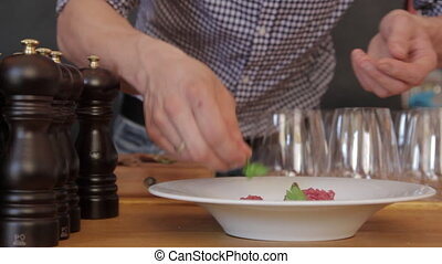 Chef serves to feed - Cook puts herbs and croutons on the...