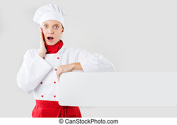 Chef showing blank sign. Woman chef, baker or cook surprise hold