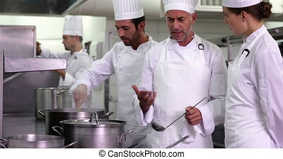 Chef showing colleague content of pot and smiling at camera...