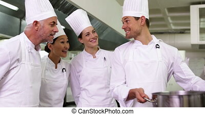 Chef showing colleagues contents of pot