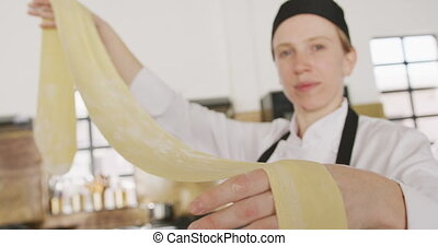 Chef showing her pasta dough - Close up front view of a ...
