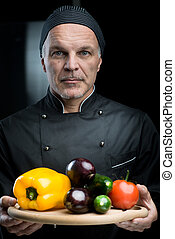 Chef showing vegetables on cutting board