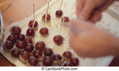 Chef skewers sticks in grapes and lays ripe grapes in the nuts and chocolate on a large silver tray