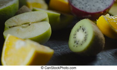 Chef Slices Kiwi on Wooden Table with Tropical Fruits
