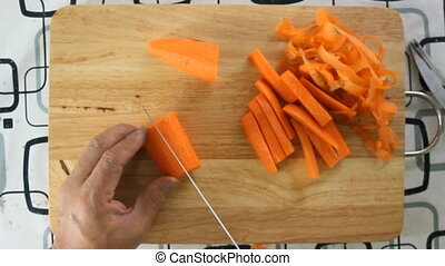 Chef slicing carrot top view