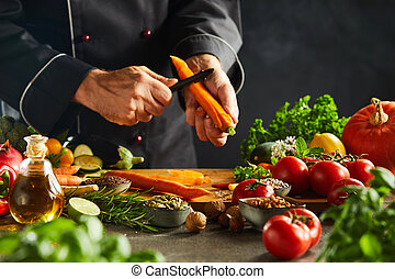 Chef slicing fresh carrots for a salad