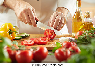 Chef slicing fresh tomatoes for a salad