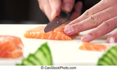 Chef slicing salmon close up.