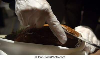 Chef slicing through the peking duck - A close up detailed...