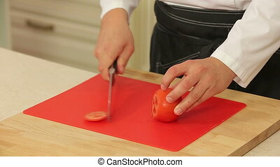 Chef slicing tomato on cutting board