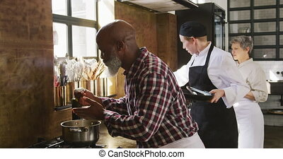 Chef smelling a cream - Side view of a senior African ...