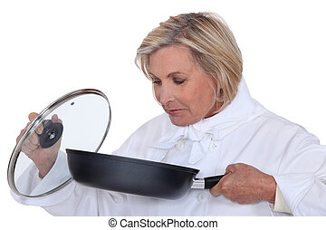 Chef smelling a saucepan