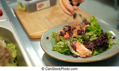 chef sprinkles pieces of dried fruit on a salad in a restaurant kitchen. cooking salad step by step