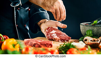 Chef sprinkling coarse salt on a ribeye steak