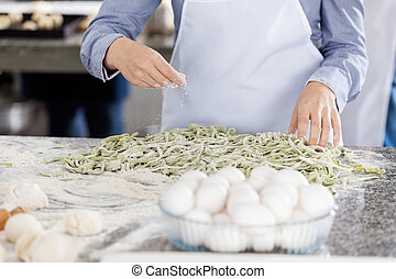 Chef Sprinkling Flour On Spaghetti Pasta At Counter In Kitchen