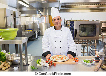 Chef standing in the kitchen with pizza - Chef standing in...