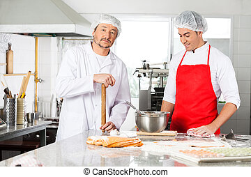 Chef Standing With Colleague Preparing Ravioli Pasta In Kitchen