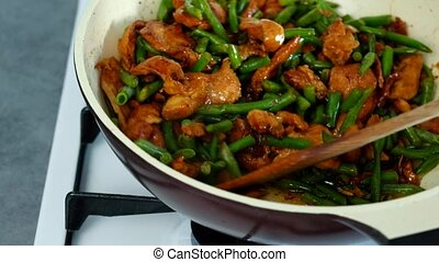 Chef stirring green beans with chicken meat in soy sauce -...