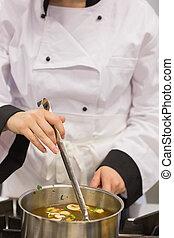 Chef stirring soup