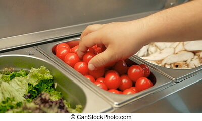 chef takes red tomatoes for salad in a restaurant kitchen. cooking salad step by step