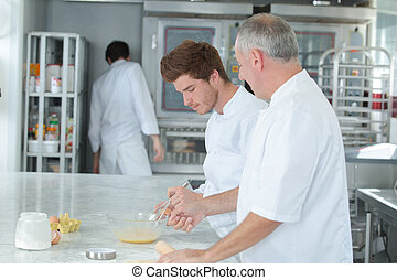 chef teaching trainee how to become a pastry chef