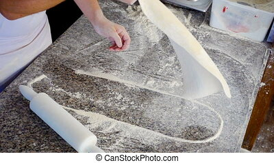 chef tosses and rolls raw very thin dough in kitchen, slow...