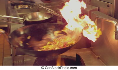 Chef tossing flaming stir fry in slow motion
