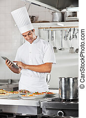 Chef Using Tablet With Pasta Dishes At Counter