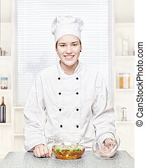 Chef with a soup of vegetables in a glass pot