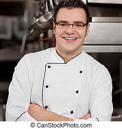 Chef With Arms Crossed Standing In Commercial Kitchen -...