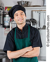 Chef With Hands Folded Standing In Kitchen - Portrait of...
