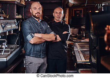 Chef with his assistant posing for a camera with his arms crossed in a restaurant kitchen.