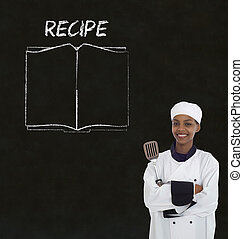 Chef with recipe book on chalk blackboard menu background