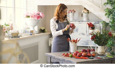 chef woman cook in apron cut pomegranate with knife neart...