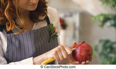 chef woman cook in apron cut pomegranate with knife closeup...
