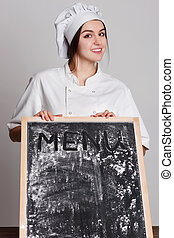 Chef. Woman cook showing empty menu chalkboard with copy space