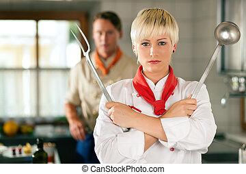 Chef - woman - in restaurant kitchen posing