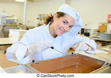 Chef working over vat of chocolate