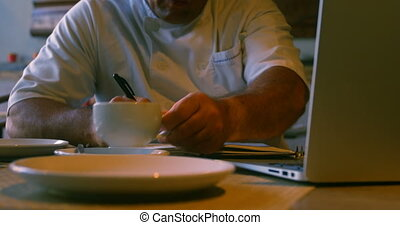 Chef writing on diary while having coffee 4k - Chef writing...