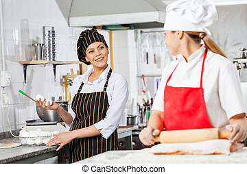 Chefs Conversing While Preparing Pasta In Kitchen