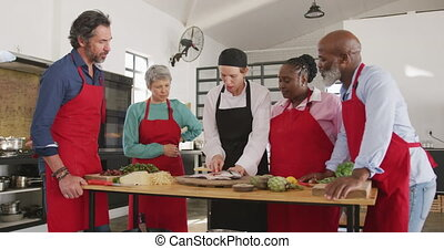 Front view of a multi-ethnic group of senior adults at a cookery class in a restaurant kitchen, the diverse group of adult students standing around a wooden table listening to a Caucasian female chef wearing chefs whites explaining and showing them how to fillet a raw fish on a wooden cutting board...