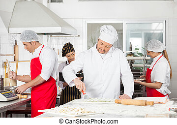 Chefs Cooking Pasta Together In Kitchen