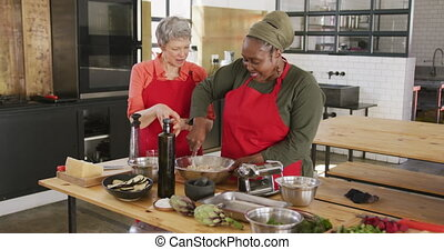Chefs cooking together - Front view of a senior African ...