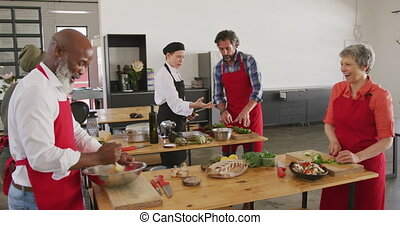 Side view of a multi-ethnic group of senior adults at a cookery class, the diverse adult students interacting with each other, cooking together and listening to instructions from a Caucasian female chef wearing chefs whites and a black hat and apron holding a tablet computer, in slow motion