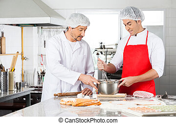 Chefs Discussing While Preparing Ravioli Pasta In Kitchen