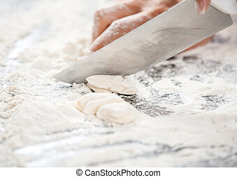 Chef's Hand Cutting Dough At Messy Counter