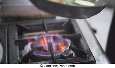Chef's hands cooking fresh vegetables in frying pan
