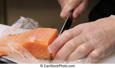 Chef's hands in gloves cutting a fresh salmon on Cutting board and pack fish In kitchen