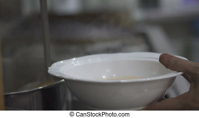 Chef's hands pouring soup into the bowl