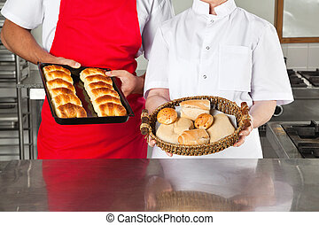 Chefs Holding Baked Breads In kitchen